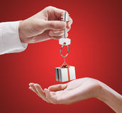 Man is handing a house key to a woman. Royalty Free Stock Image