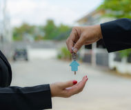 Man handing a house key to a woman Royalty Free Stock Image