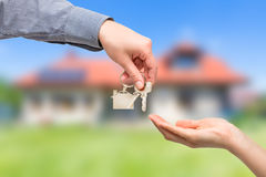 Man is handing a house key to a woman. Real estate concepts. Royalty Free Stock Photos