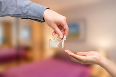 Man is handing a house key to a woman. Real estate concepts. Stock Image
