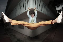 Man handing from a ledge. Man in funky clothing hanging from a ledge Royalty Free Stock Images