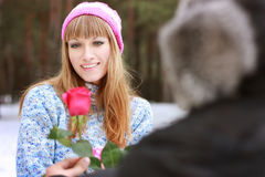 Man handing over a single red rose to young woman Royalty Free Stock Photos