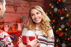 Man handing red wrapped gift to a beautiful woman. Man handing gift box to a beautiful smiling blond woman. Christmas love concept Stock Photo