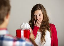 Man handing woman gift. Man handing red wrapped gift to a beautiful woman Royalty Free Stock Image