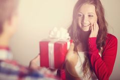 Man handing woman gift. Man handing red wrapped gift to a beautiful woman Stock Images