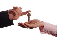 Man handing a women a set of keys. On white stock photos