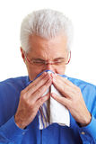 Man with handkerchief. Senior citizen blowing his nose with an handkerchief Royalty Free Stock Photos