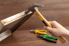 Man handle hammer to hit or fix stainless tray on wooden backgroud Stock Image