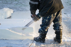 Man handles the ice chainsaw. Man handles using chainsaws block of ice Stock Photo