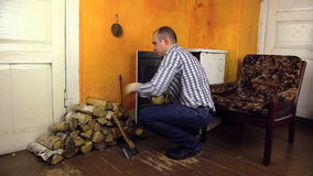 Man handles wood in pile near old stove in living rural room stock video