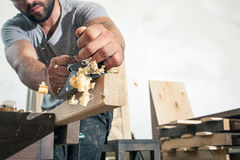 Man handles a wooden bar with a black jack plane Stock Images