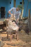 A man handles a wooden sculpture in the Studio. Vietnam Royalty Free Stock Image