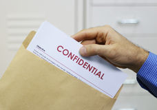 Man handling confidential documents. Cropped view image of a man handling confidential documents placing them inside a brown manilla envelope for mailing Royalty Free Stock Photography