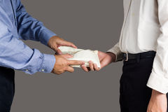 Man handling an envelope full of money to another person Stock Photography