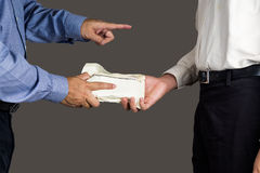 Man handling an envelope full of money to another person with finger pointing Royalty Free Stock Photos