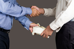 Man handling an envelope full of money to another person with hand shake stock image