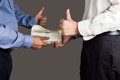 Man handling an envelope full of money to another person with thumbs up Stock Photography
