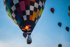 A person pulling on a rope to handle his hot air balloon after a flight through the sky. stock photo