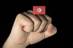 Man handnäven med den tunisiska flaggan som isoleras på svart Royaltyfri Bild