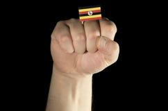 Man handnäven med den ugandiska flaggan som isoleras på svart Royaltyfri Fotografi