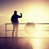 Man at handrail on mole take photos over sea to morning horizon. Tourist photograph. Sunny blue sky, smooth water level royalty free stock photos