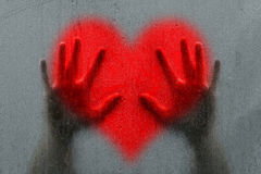 Man hands on blurry red heart symbol Royalty Free Stock Photo
