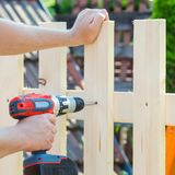Man hands building wooden fence with a drill and screw. DIY concept. Close up of his hand and tool. Man hands building wooden fence with a drill and screw. DIY stock photos