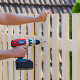 Man hands building wooden fence with a drill and screw. DIY concept. Close up of his hand and tool. Man hands building wooden fence with a drill and screw. DIY stock image