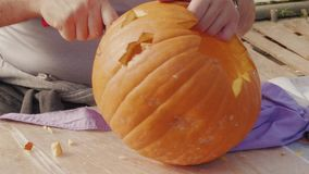 Man hands carving pumpkin for Halloween jack-o`-lantern