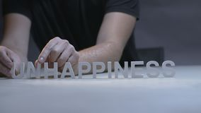 Man hands changing word happiness for unhappiness by letters on gray background stock video