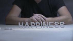 Man hands changing word unhappiness for happiness by letters on gray background stock video