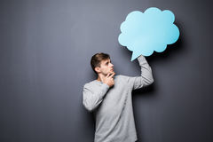 Man with hands on chin holding blue blank speech bubble with space for text on grey background Royalty Free Stock Image