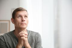 Man with hands clasped together for prayer near window. Space for text royalty free stock image