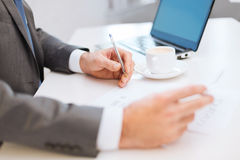 Man hands with contract and pen, coffee and laptop. Business, technology and internet concept - close up of man hands with contract and pen, coffee and laptop Royalty Free Stock Photo
