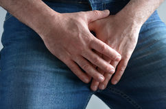 Man hands covering his painful crotch. Close up on a man hands covering his painful crotch. Male healthcare concept Stock Images