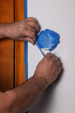 Man hands is covering thermostat with masking tape Royalty Free Stock Photo
