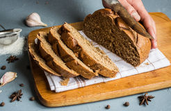 Man hands cut with knife piece of rye bread Stock Photos