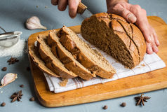 Man hands cut with knife piece of rye bread Stock Photography