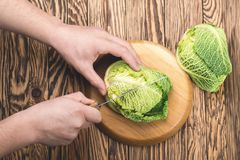 Man hands cutting fresh cabbage for salad, close up. Royalty Free Stock Photography