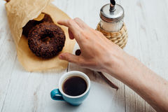 Man hands eating chocolate donut with coffee on wooden table Royalty Free Stock Photography