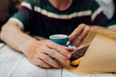 Man hands eating chocolate donut with coffee on wooden table Stock Image