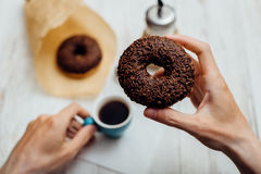 Man hands eating chocolate donut with coffee on wooden table Royalty Free Stock Photo