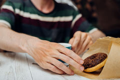 Man hands eating chocolate donut with coffee on wooden table Royalty Free Stock Photos