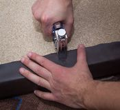 Man hands fastening leather to the particle board using stapler stock photos