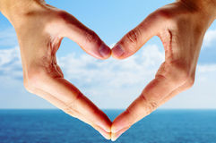 Man hands forming a heart. With the ocean and the sky in the background royalty free stock photos