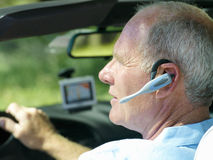 Man with hands-free device in car, side view Royalty Free Stock Images