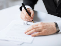 Man hands with gambling dices signing contract Stock Image