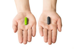 Man hands giving two big pills. Green and black. Make your selection. health or death. Choose your side Royalty Free Stock Photo