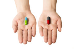 Man hands giving two big pills. Green blue and red black. Make your selection. healthy lifestyle or bad habits. Choose your side. Man hands giving two big pills Stock Photography