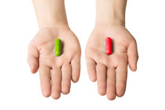 Man hands giving two big pills. Green and red. Make your selection. healthy lifestyle or bad habits. Choose your side Stock Photos